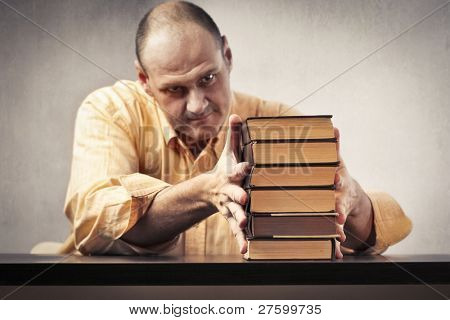 Teacher putting in order a stack of books