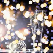Two Glasses Of Champagne With Christmas Toys. Festive Lights Bokeh Background poster