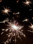 Beautiful Sparkler Firework Flame On Black Background. Closeup Of Sparks Glimmering In Night While F poster