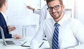 Business People At Meeting In Office. Focus At Cheerful Smiling Bearded Man Wearing Glasses. Confere poster