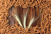 Top View Of Raw Wholemeal Pasta From Fusilli, On A Wooden Background With Wheat Boughs poster