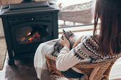 Human with cat relaxing in wicker armchair by the fire place in wooden cabin. Warm and cozy winter h poster