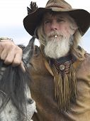 picture of wild west  - Rugged authentic cowboy with his horse wearing traditional clothing - JPG