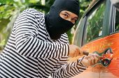 Thief In Black And White Jacket Using Screwdriver To Open Orange Car Door To Stealing A Car On Stree poster