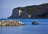fisher boat leaving harbor of Agios Stefanos along huge cliffs