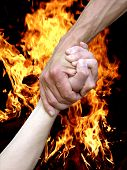 stock photo of fire extinguishers  - Hand in a hand on a background a fire - JPG