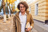 Portrait Of Handsome Young Man With Books Outdoors. College Male Student Carrying Books In College C poster