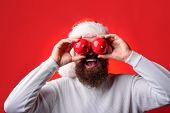 Joyful Man With New Year Toys Near Eyes. Winter Holidays. Bearded Santa Man Hold Christmas Balls Dec poster