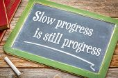 Slow progress is still progress - inspirational writing on a slate blackboard poster