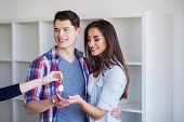 New Home. Funny Young Couple Enjoy And Celebrating Moving To New Home. Happy Couple At Empty Room Of poster