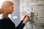 Woman Entering Security Pin On Home Alarm Keypad. poster