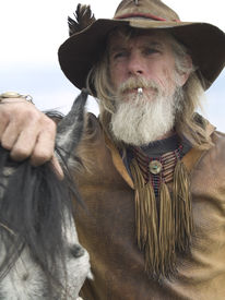 image of wild west  - Rugged authentic cowboy with his horse wearing traditional clothing - JPG
