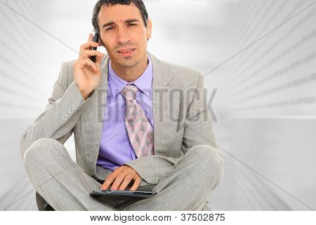Portrait of a  young businessman, at corporate sitting and using a tablet PC