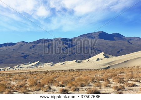 Cold morning in the desert. The famous Eureka - a giant sand dune in California. Background - dark black mountains