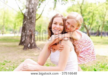 mother and daughter sitting together on the grass