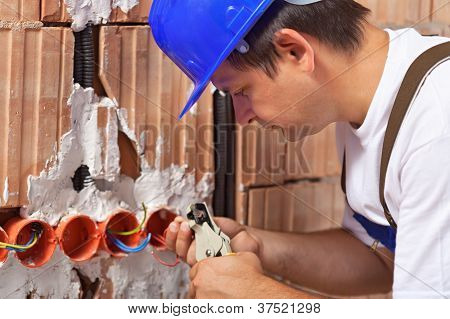 Worker Installing Electrical Wires In Building Wall