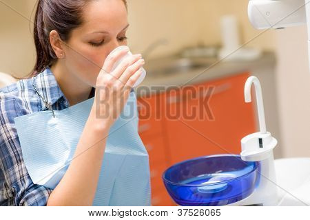 At the dentist dental patient woman rinse mouth after treatment