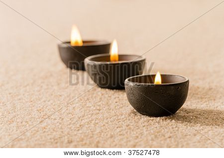 Spa therapy three candles on sand still nature
