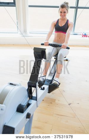 Woman sitting at the row machine at the gym smiling and pulling