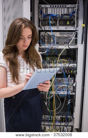 Woman checking servers using tablet pc in data center