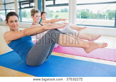 Happy women doing boat pose in yoga class in fitness studio