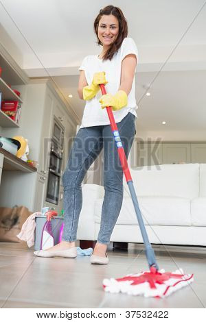 Brunette woman mopping the floor while smiling