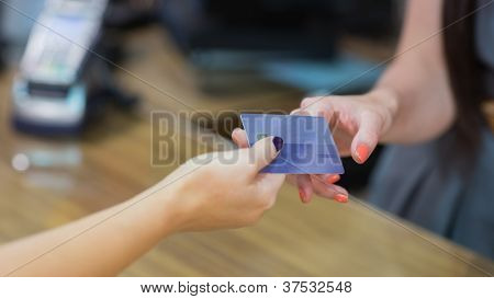 Woman handing over credit card at cash register