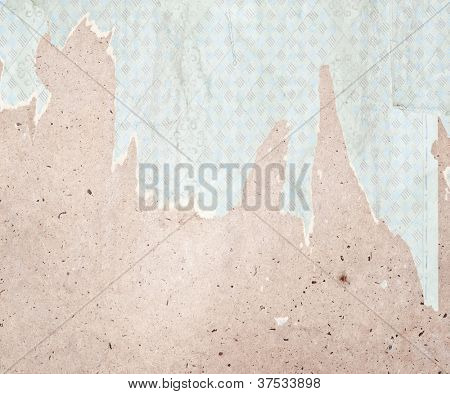 Fragment of old destroyed wall with wallpaper in abandoned house