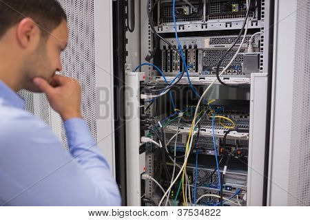 Man looking at rack mounted servers in data centre