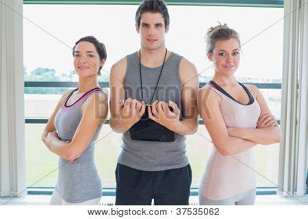 Trainer standing between two women in fitness studio