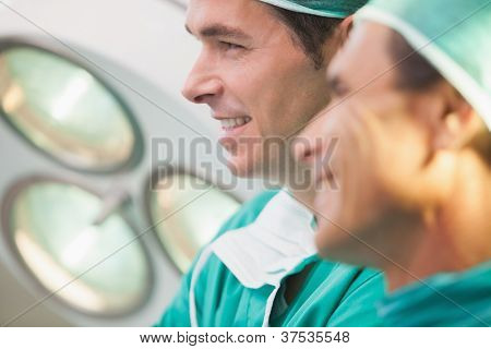 Two surgeons smiling in operating theatre