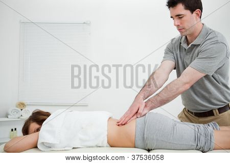 Man standing while massaging the back of a woman in a room