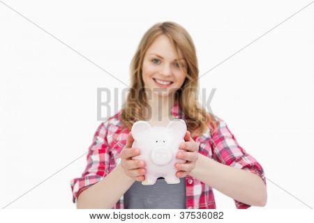 Woman holding a piggy bank while smiling against a white background