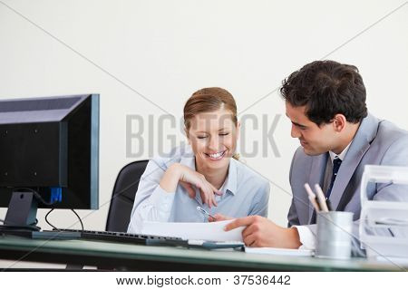Businessman showing something to a colleague  against grey background