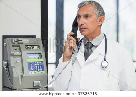 Doctor on a payphone in hospital corridor