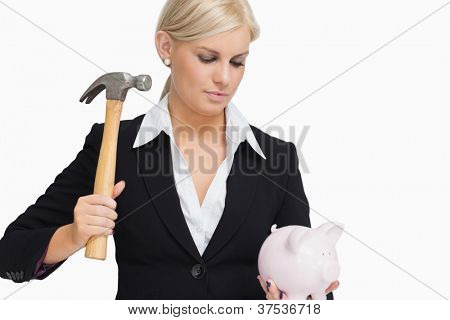 Serious businesswoman holding a piggy-bank and hammer against white background