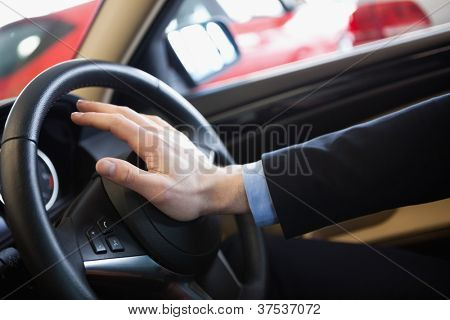 Man honking the horn in a car dealership