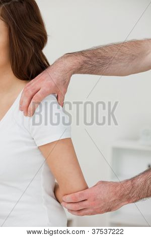 Close-up of a doctor examining the shoulder of a patient in a room
