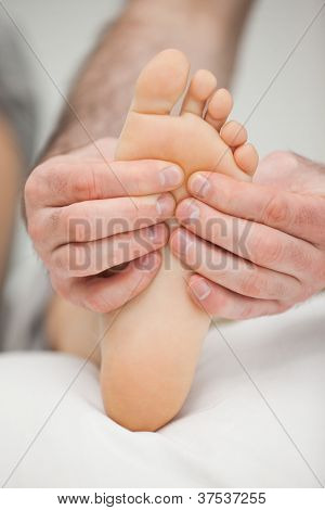 Fingers palpating the sole of a foot in a room