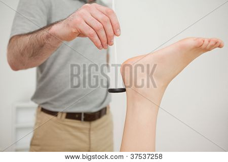 Reflex hammer being held by a doctor in a medical room