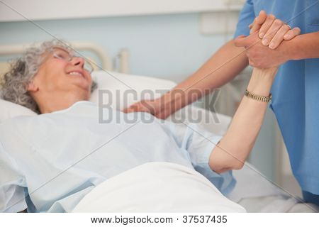Elderly pateint in hospital bed holding hand of nurse