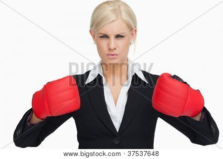 Serious businesswoman wearing red gloves against white background