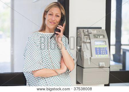 Smiling female patient using payphone in hospital corridor