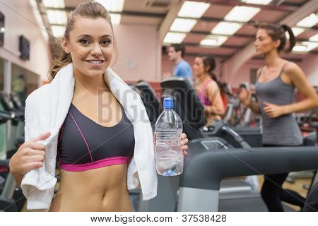 Woman smiling and drinking a bottle of water in the gym after exercise