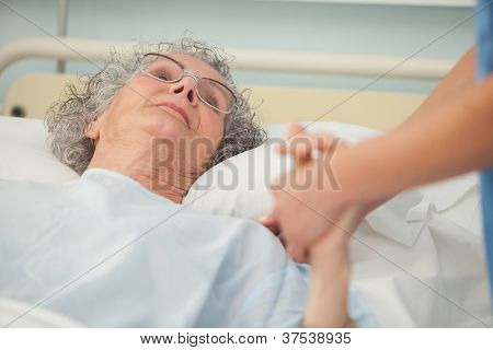 Nurse caring about old woman lying in bed
