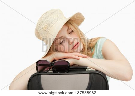 Woman asleep while leaning on a suitcase against white background