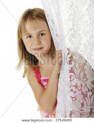 Portrait of a pretty young elementary girl peeking from behind a lace curtain.  On a white background.