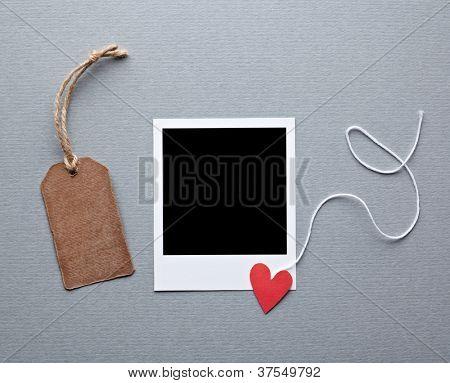 Frame da foto instantânea com marca presente em branco e pequena coração vermelho. Fundo de papel cinza.