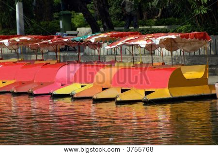 Pedalos With Canopies At The Side Of A Lake. Reflection