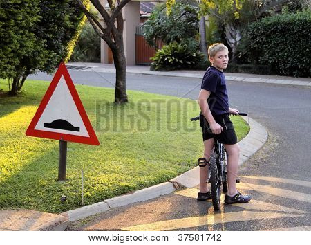 Young Boy Stopped Bicycle At Speed Bump